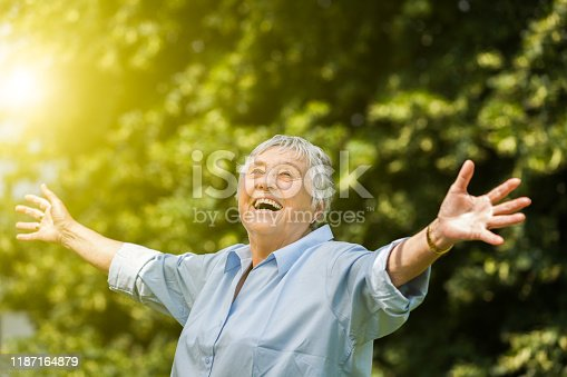 Happy senior woman portrait, outdoors in garden
