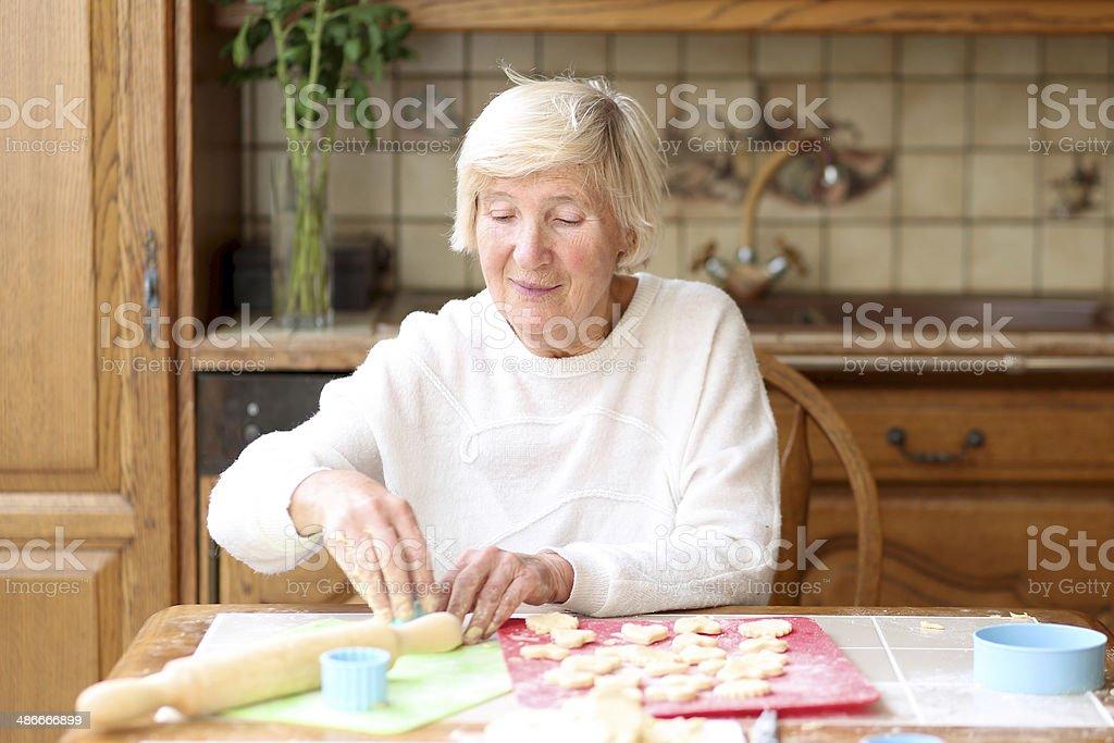 Happy senior woman preparing delicious cookies for her grandchildren stock photo