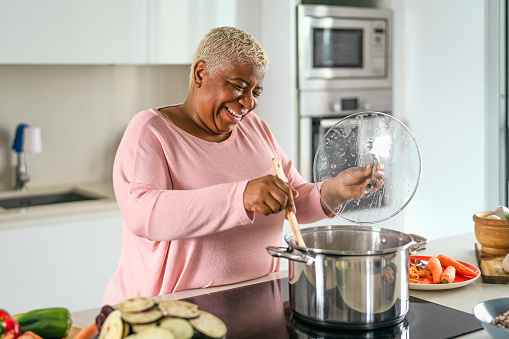 Happy senior woman preparing lunch in modern kitchen - Hispanic Mother cooking for the family at home