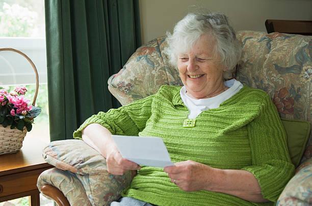 Happy senior woman reading a letter stock photo