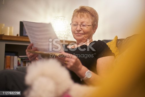 A happy smiling senior woman reading through a letter