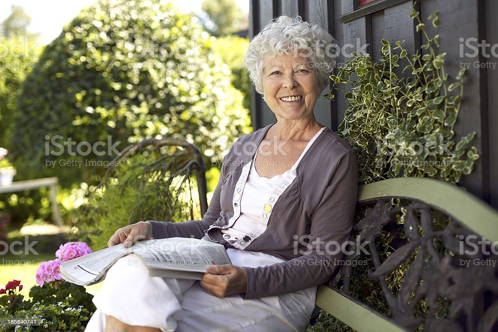 Happy senior woman reading newspaper in her backyard stock photo