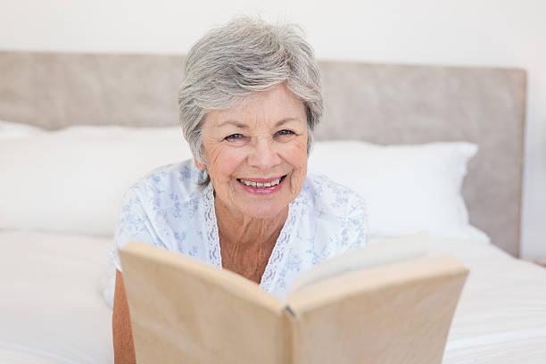 happy senior woman reading story book - kurzgeschichten stock-fotos und bilder