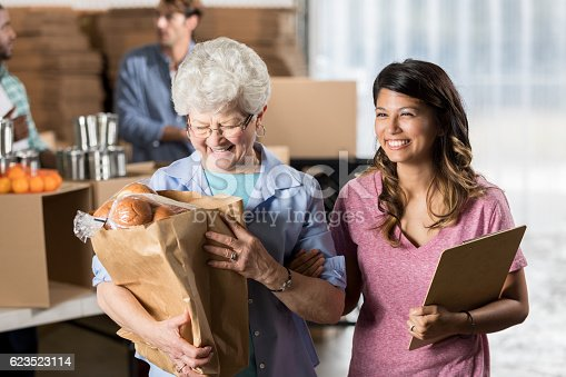 istock Happy senior woman receives donations during food drive 623523114