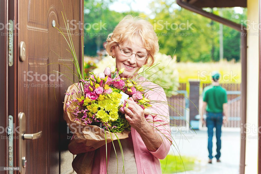 Happy senior woman receiving flowers Happy senior woman standing in an entance door, holding a bouquet of flowers and reading label. Delivery man in the background.  60-64 Years Stock Photo
