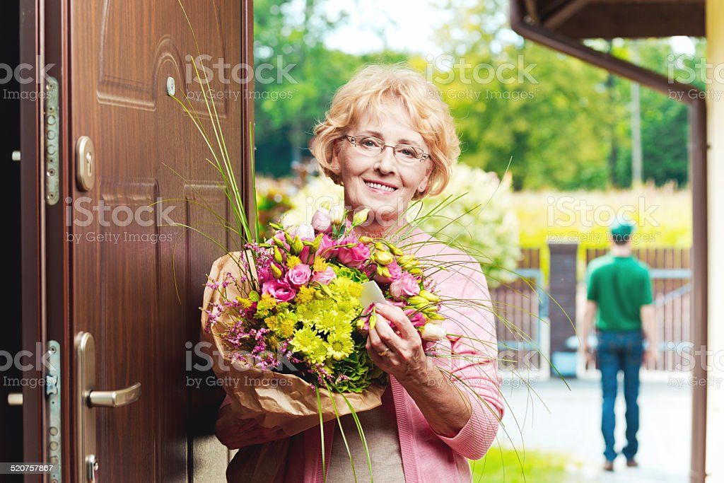 Happy senior woman receiving flowers Happy senior woman standing in an entance door, holding a bouquet of flowers and smiling at camera Delivery man in the background.  60-64 Years Stock Photo