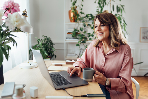 Beautiful smiling mature woman sitting in the comfot of her home office and working, social distancing concept.