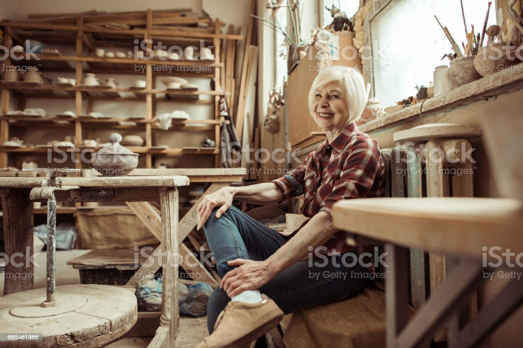Happy senior woman sitting on bench near window at workshop foto de stock royalty-free