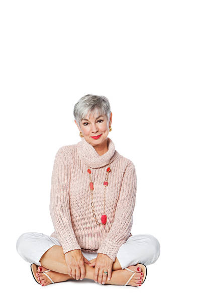 Happy Senior Woman Sitting On Floor Full length portrait of happy senior woman sitting on floor isolated on white background. Vertical shot cross legged stock pictures, royalty-free photos & images