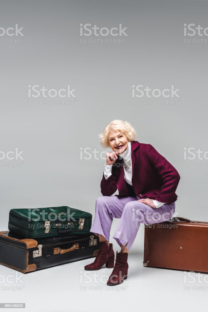 happy senior woman sitting on vintage suitcase on grey zbiór zdjęć royalty-free