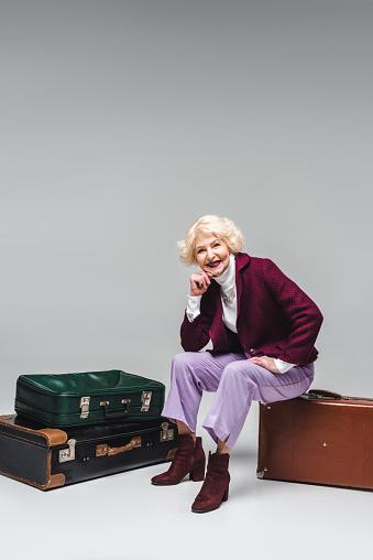 Photo libre de droit de Heureuse Femme Senior Assis Sur La Valise Vintage Sur Fond Gris banque d'images et plus d'images libres de droit de {top keyword}
