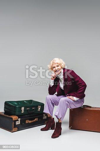 Happy Senior Woman Sitting On Vintage Suitcase On Grey - Stockowe zdjęcia i więcej obrazów Bagaż