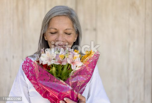 Happy senior woman smelling a beautiful flower bouquet with eyes closed - Headshot