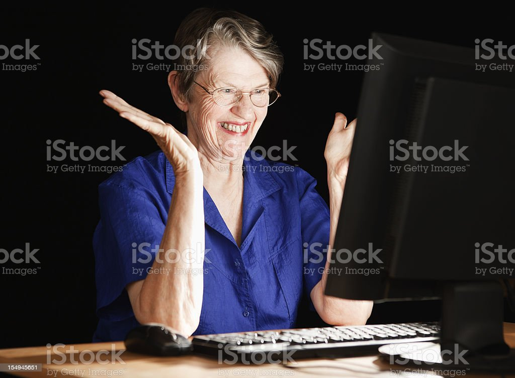 Happy senior woman smiles in delight at her computer monitor royalty-free stock photo