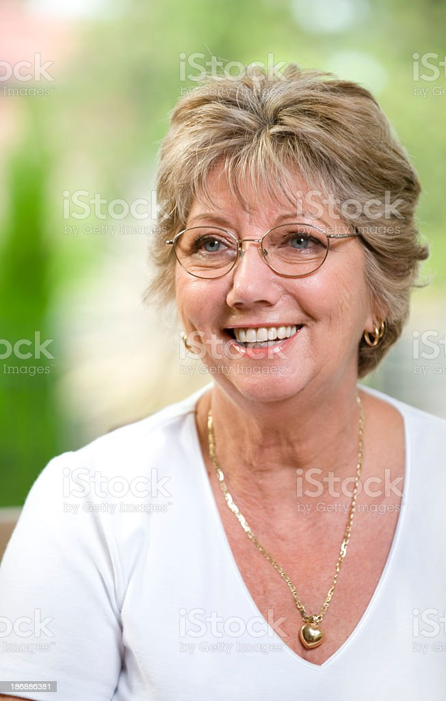 Happy senior woman smiling Happy senior woman smiling with glasses on 55-59 Years Stock Photo
