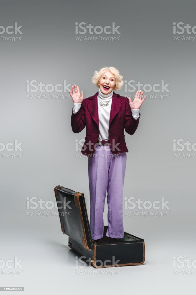 happy senior woman standing inside of vintage suitcase with raised hands on grey royalty-free stock photo