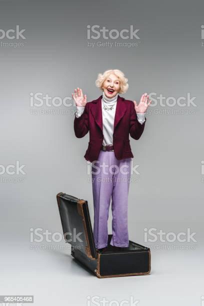 Glücklich Senior Frau Stehen Innerhalb Des Vintage Koffer Mit Erhobenen Händen Auf Grau Stockfoto und mehr Bilder von Aktiver Senior