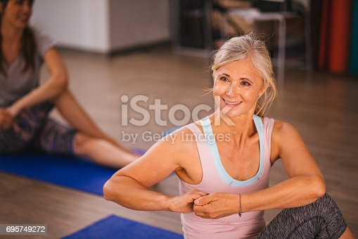istock Happy senior woman stretching and keeping fit by doing yoga 695749272