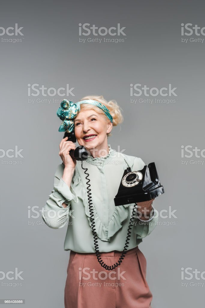 happy senior woman talking by rotary phone isolated on grey royalty-free stock photo
