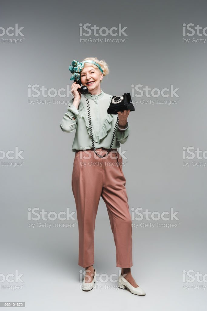 happy senior woman talking by rotary phone on grey royalty-free stock photo