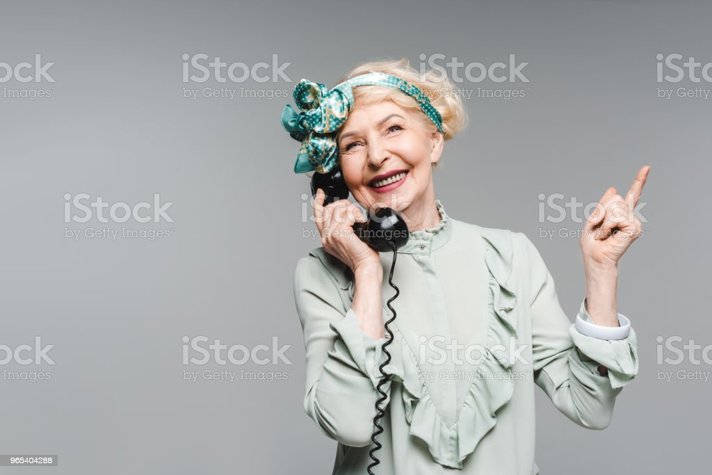happy senior woman talking by vintage phone and pointing up isolated on grey zbiór zdjęć royalty-free