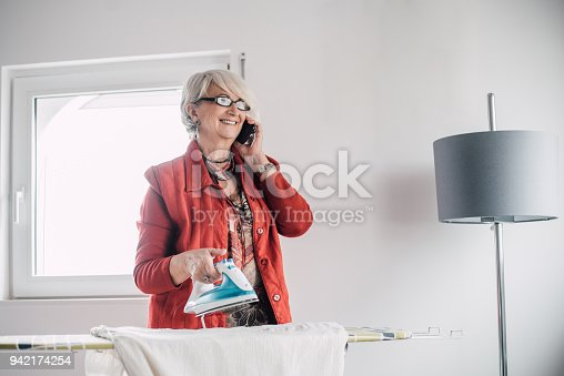 524159504 istock photo Happy senior woman talking on a phone and ironing 942174254