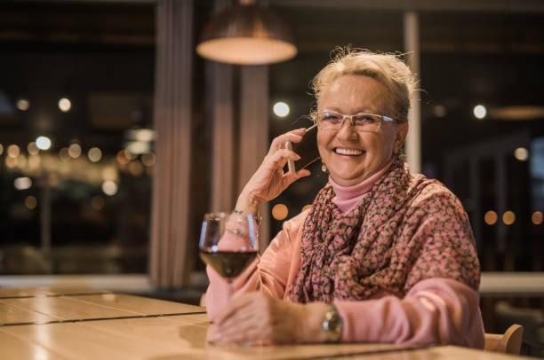 mujer senior feliz riendo y hablando por un teléfono - antigua yugoslavia fotografías e imágenes de stock