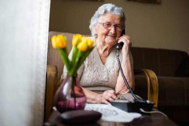 szczęśliwa starsza kobieta rozmawia przez telefon w salonie. - dojrzały zdjęcia i obrazy z banku zdjęć