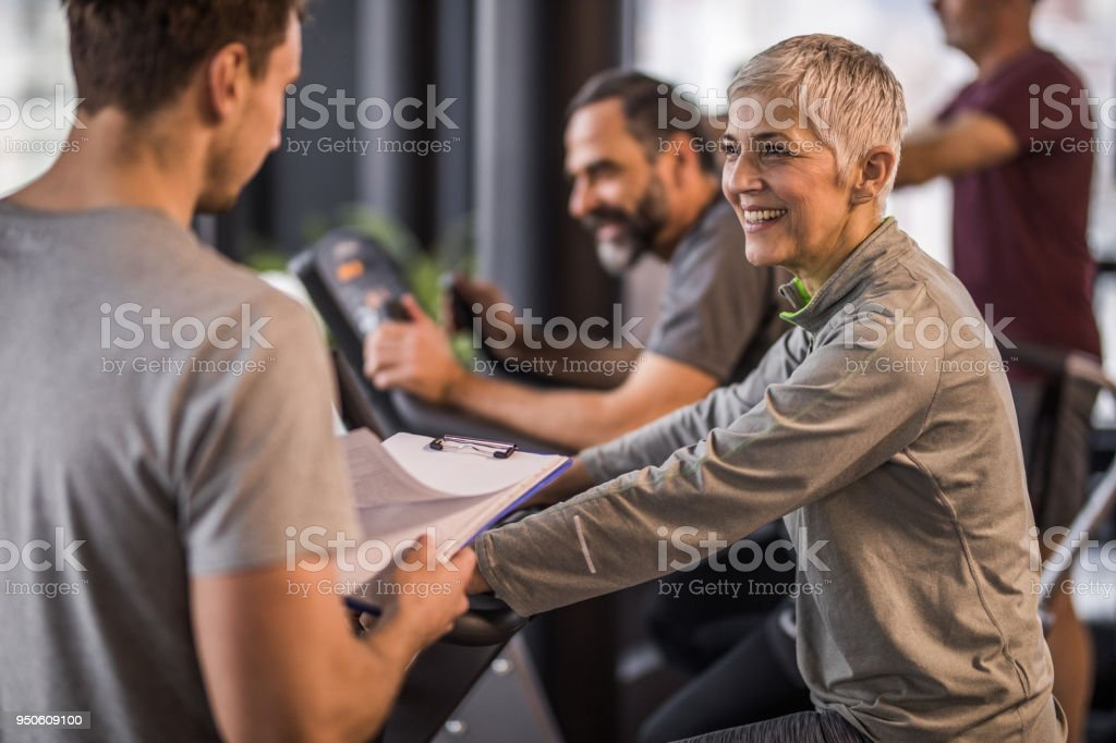 Happy senior woman talking to her coach on a spinning class in a gym. stock photo