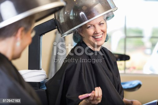 istock Happy senior woman talking with friend in beauty salon 512942163