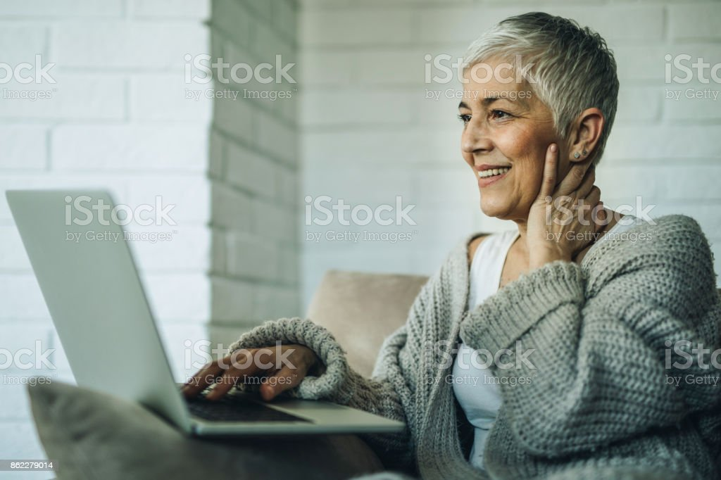Happy senior woman using laptop while relaxing at home. stock photo
