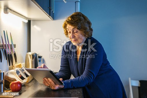 Happy senior woman using tablet in her kitchen