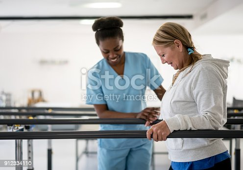 istock Happy senior woman walking between parallel bars at physiotheray with her therapist next to her 912334110
