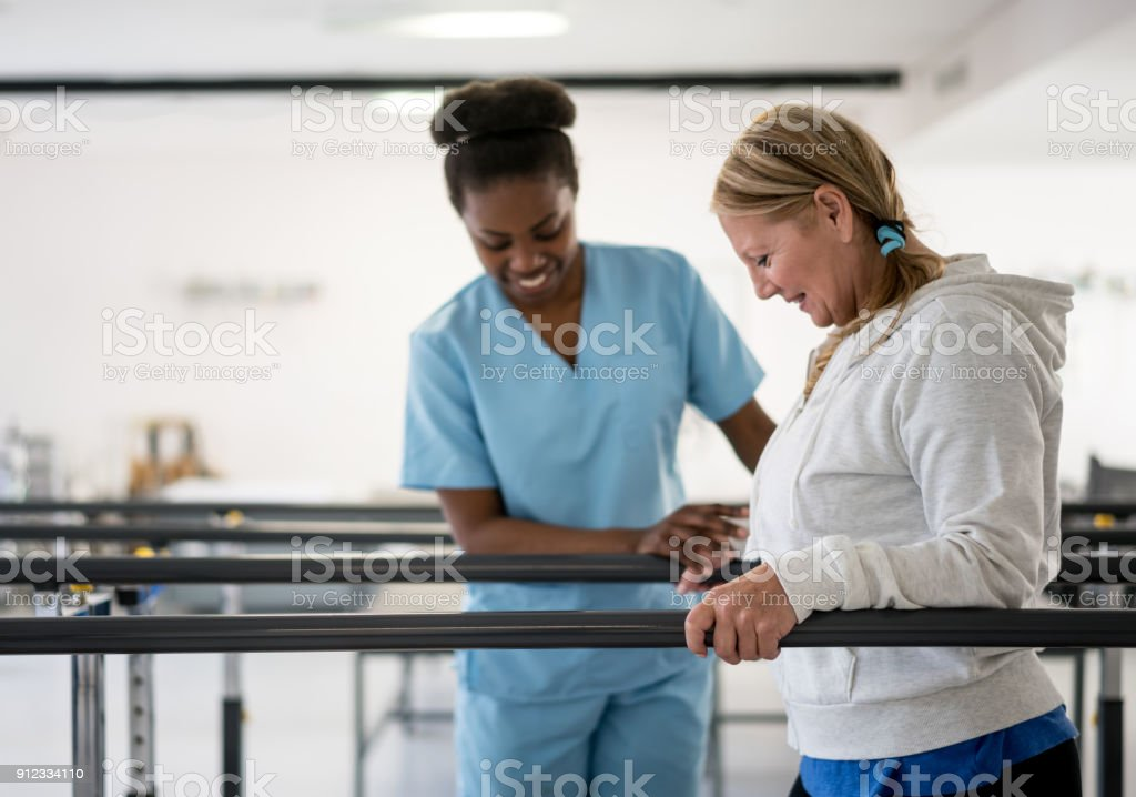 Happy senior woman walking between parallel bars at physiotheray with her therapist next to her stock photo