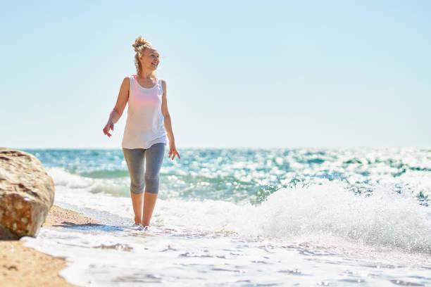 Feliz mujer mayor camina por el mar. - foto de stock