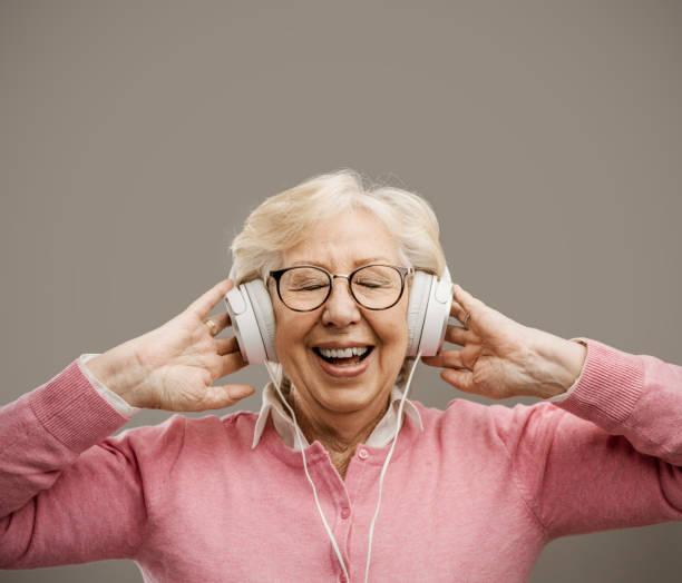 Glückliche ältere Frau trägt Kopfhörer – Foto