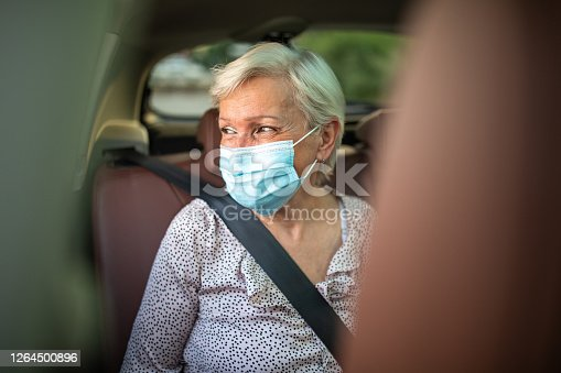 Portrait of senior woman with short, white hair, wearing protective face mask, sitting on back seat of car during a ride, with fastened seat belt, looking through the window and smiling. Ride-sharing concept