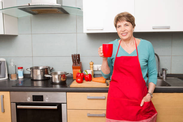 Happy Senior woman  with a cup of tea in hand  in the kitchen. stock photo
