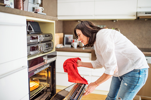 Happy senior woman with a red kitchen cloth opening an oven door.