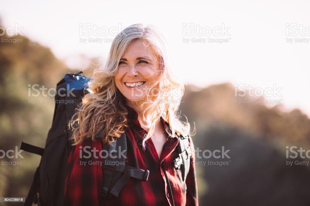 Glückliche ältere Frau mit Rucksack wandern in den Bergen – Foto