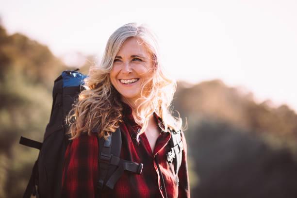 feliz mujer senior con mochila de senderismo en las montañas - mochilero fotografías e imágenes de stock