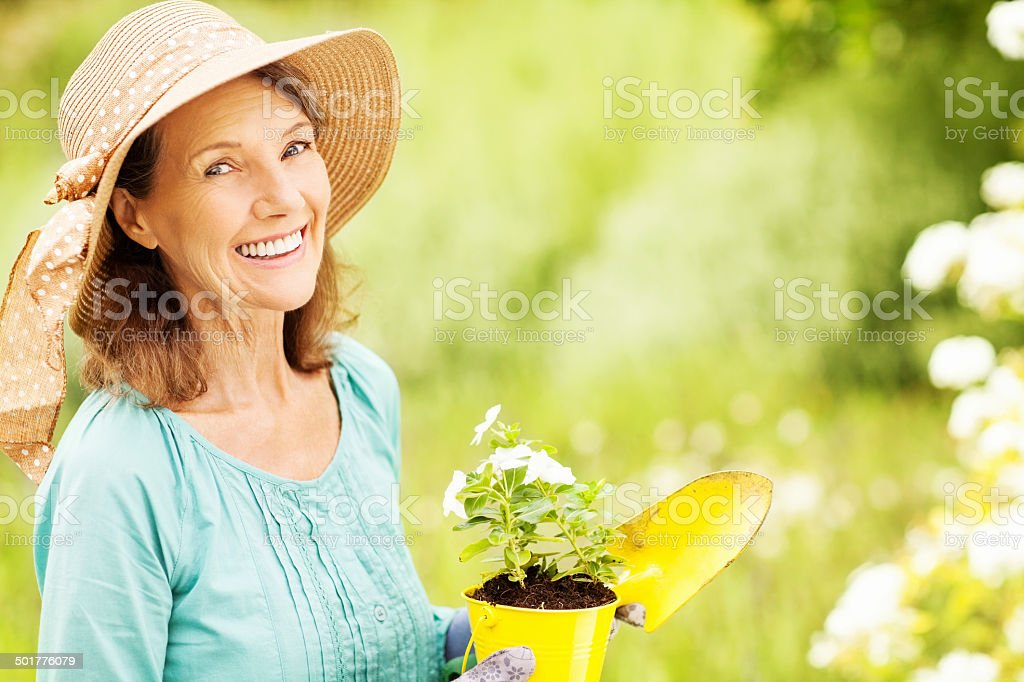Happy Senior Woman With Flower Pot And Shovel In Garden stock photo