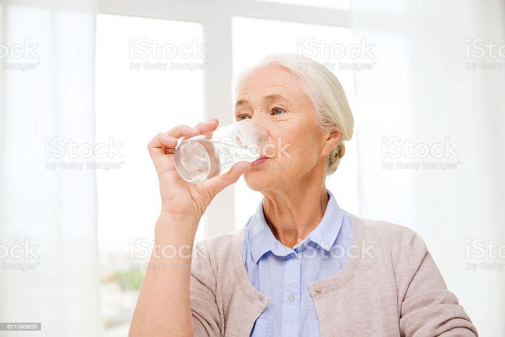 happy senior woman with glass of water at home stock photo