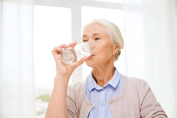 happy senior woman with glass of water at home - drinking water stock photos and pictures