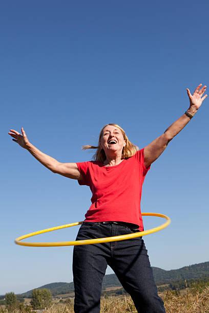 glückliche senior frau mit korb. übung. - hula hoop workout stock-fotos und bilder