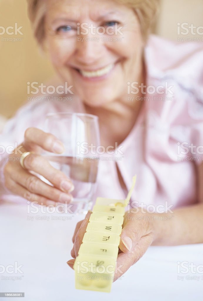Happy senior woman with medicine and  glass of water royalty-free stock photo