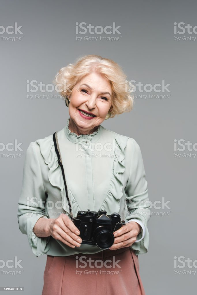 happy senior woman with vintage film camera isolated on grey zbiór zdjęć royalty-free