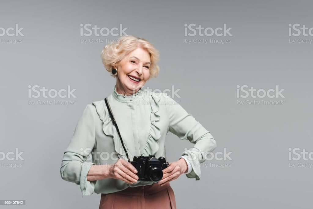 happy senior woman with vintage film camera isolated on grey zbiór zdjęć royalty-free