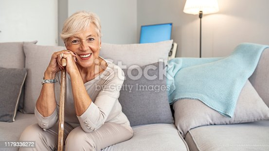 Smiling grandmother sitting on couch. Portrait of a beautiful smiling senior woman with walking cane on light background at home. Old woman sitting with her hands on a cane