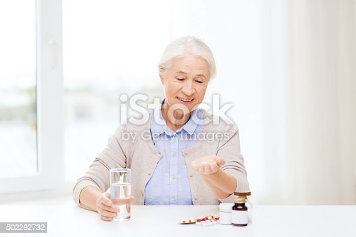 istock happy senior woman with water and medicine at home 502292732